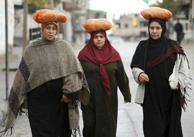 Palestinian women walk in a street after buying bread from a bakery in Jabalya in the northern Gaza Strip January 1, 2009. Israeli aircraft attacked government buildings in the Gaza Strip on New Year's Day and Hamas fired more rockets at Israel after both foes spurned international calls for a ceasefire.
