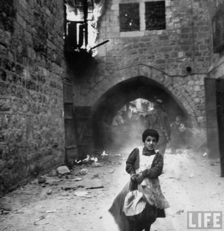 28 maj 1948 - den judiska flickan Rachel Levy (7 år) flyr från en gata med brinnande byggnader då araberna plundrar Jerusalem efter stadens kapitulation.